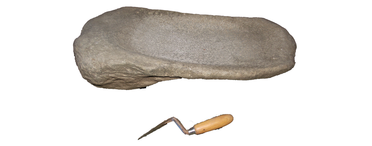 Saddle quern, with trowel as scale