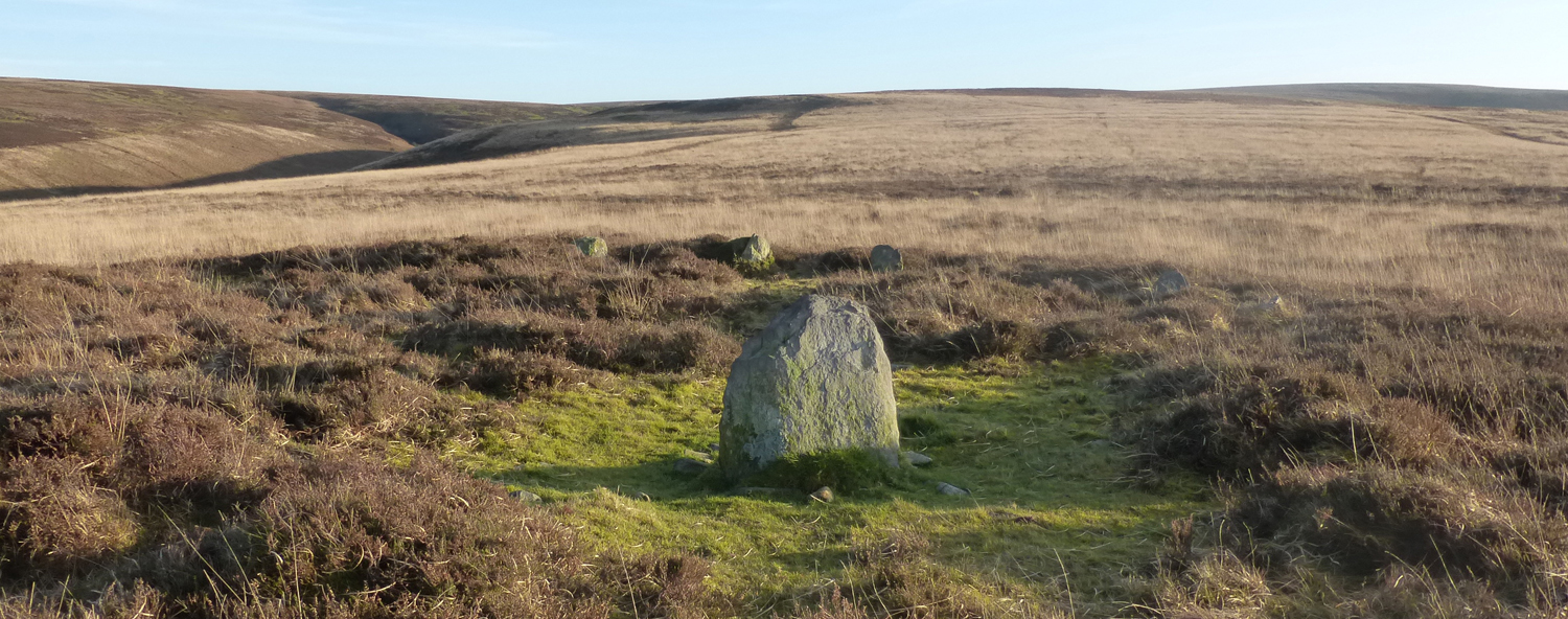 Cairn, bordered by more upright stones, set within a moorland landscape